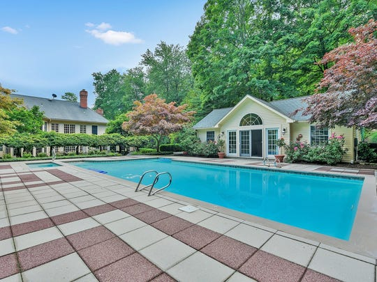The backyard offers an in-ground pool surrounded by patios, a one-bedroom guest house and a private pond.