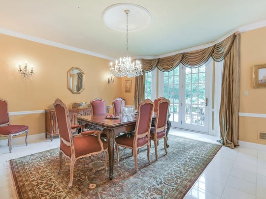 The dining room has chair rails, wall sconces, a crystal chandelier and floor-to-ceiling windows, including a French door.