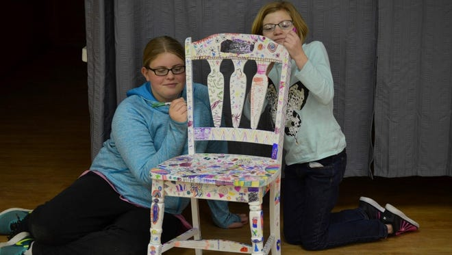 Girl Scouts Emma Meisner, left, and Emily Weir work on one of the collaborative pieces that will part of the Girl Empowerment Exhibit.
