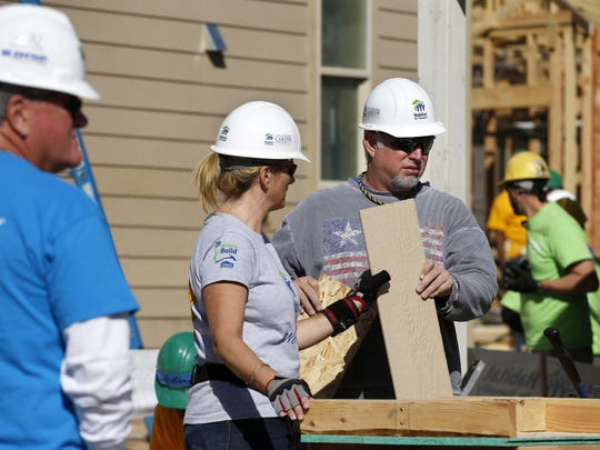 Country musicians Garth Brooks and Trisha Yearwood volunteer at a Habitat for Humanity construction site in the Globeville neighborhood of Denver on Oct. 9, 2013. The couple joined former President Jimmy Carter and his wife, Rosalynn, in commemorating the Carters' three-decade relationship with Habitat for Humanity by helping build affordable housing in the Denver area.