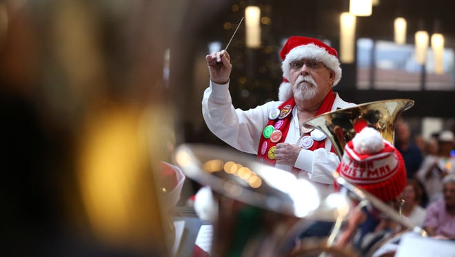 Jeff Stone, from Texas A&M University-Kingsville, conducts the first section of music during the 28th annual Tuba Christmas in the lobby of the Plains Capital Bank on Friday, Dec. 22, 2017. Musicians ages 12 to 71 participated in the concert.