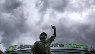 Heavy clouds cover the sky above TD Ameritrade Park and The Road to Omaha statue, during a weather delay in the NCAA College World Series baseball elimination game between Oregon State and Washington, in Omaha, Neb., Monday, June 18, 2018. (AP Photo/Nati Harnik)