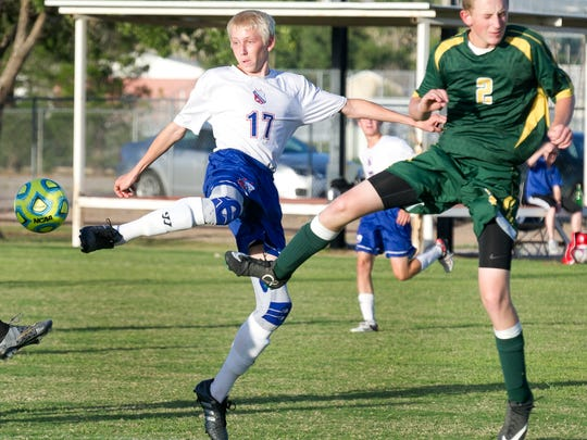 Las Cruces High's Lucas Kirby goes airborne for the ball against Mayfield defender Derek Achen Thursday night at the Field of Dreams Soccer Complex.