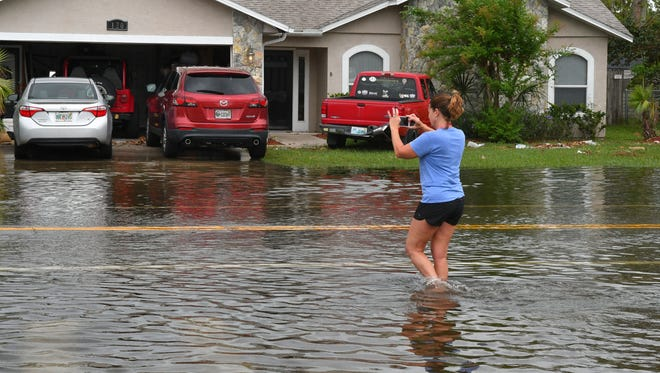 Cone Road. Wendy Rothwell takes photos of the flooding of her street in Merritt Island on Monday following the heavy rains that hit Brevard on Sunday.