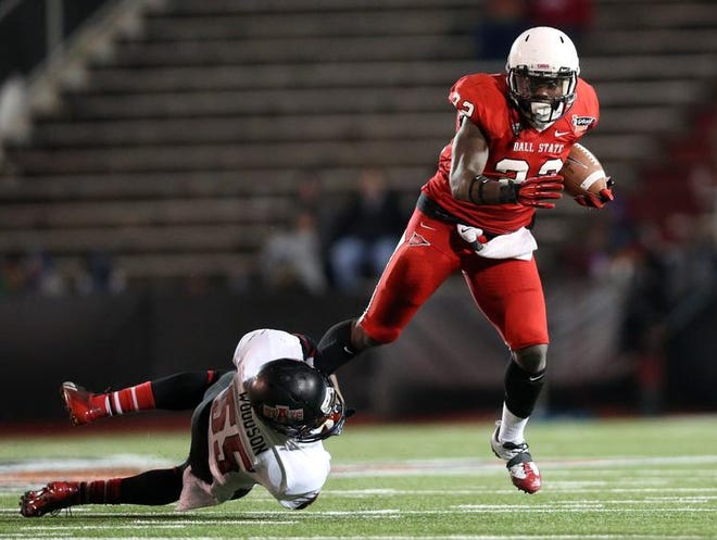 Ball State Cardinals running back Jahwan Edwards (right) is tackled by Arkansas State Red Wolves linebacker Xavier Woodson (55) in the second half of Sunday's GoDaddy Bowl.