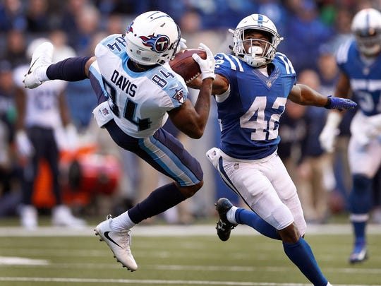 Tennessee Titans wide receiver Corey Davis (84) makes a catch behind Indianapolis Colts defensive back Kenny Moore (42) in the second half of their game at Lucas Oil Stadium Sunday, Nov. 26, 2017. The Tennessee Titans defeated the Indianapolis Colts 20-17.