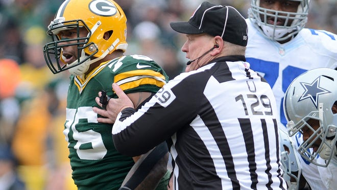 Livonia native Bill Schuster, in his 15th season as an NFL umpire, holds back Mike Daniels as the Green Bay Packers defensive lineman jaws with members of the Cowboys during the first quarter of Sunday's divisional playoff game Jan. 16, 2015. The Packers won 26-21.