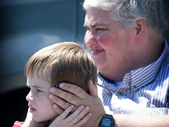 Jeff Clark holds tight to his son, Steven, 6, as the