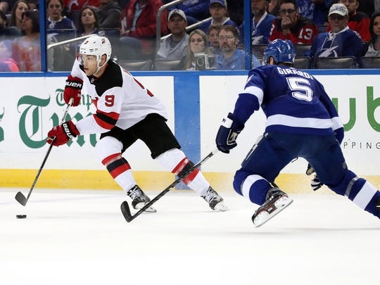 Feb 17, 2018; Tampa, FL, USA; New Jersey Devils left wing Taylor Hall (9) skates with the puck as Tampa Bay Lightning defenseman Dan Girardi (5) defends during the first period at Amalie Arena.