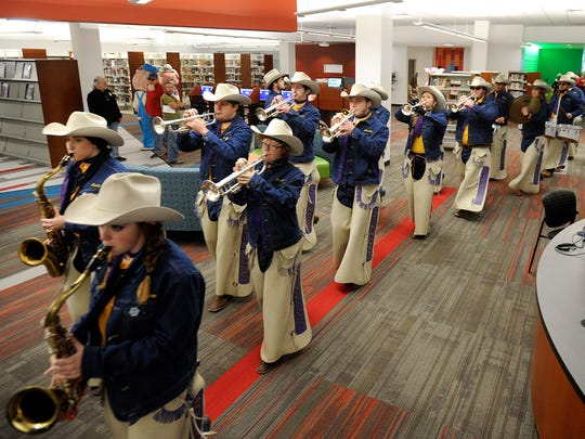 The Hardin-Simmons University Cowboy Band marches through the south branch of the Abilene Public Library to celebrate the library's opening at it new location at the Mall of Abilene on Saturday, Nov. 19, 2016.