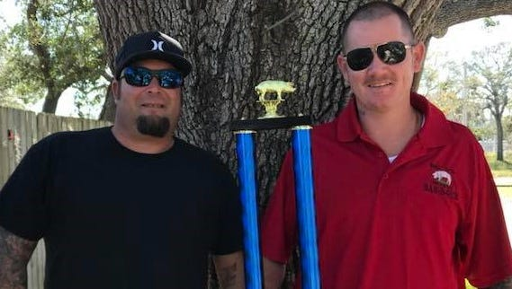 Mike Payton and Dusty McAlister are friends most of the time, but not when it comes to a barbecue competition. McAlister shows off his trophy for winning the pork competition in last year's Backyard BBQ Cook-Off.