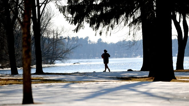 A silhouetted runner enjoys Monday's spring like weather in Wisconsin Rapids while jogging in shorts along the Wisconsin River.