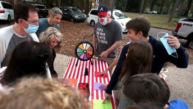 Andy McMurry spins the wheel for family playing Fat Albert at their fair-themed birthday celebration on Thursday.