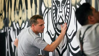 Artist Shepard Fairey works on a mural in The Belt alley May 16, 2015, in Detroit
