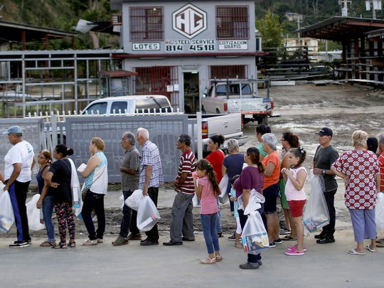 People wait on line for free food and health supplies passed out by the nonprofit Lets Give on December 19, 2017 in Utuado, Puerto Rico.