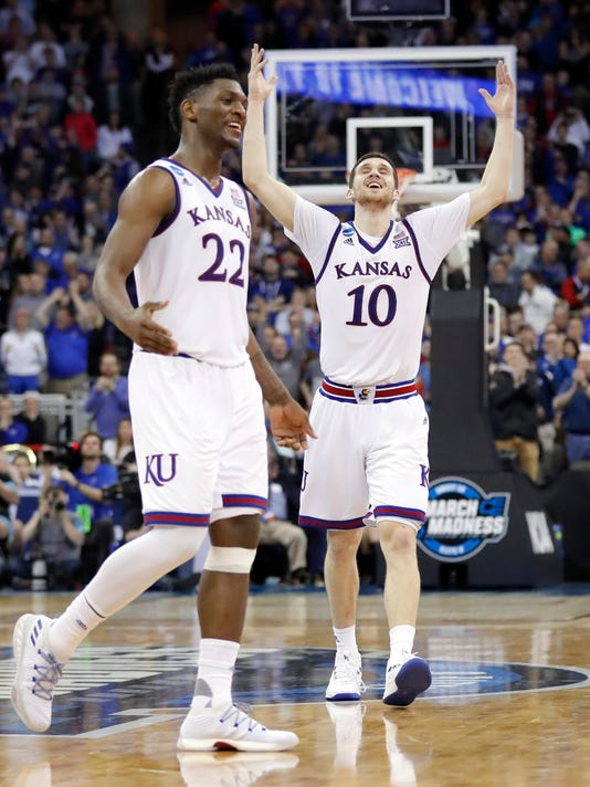 Kansas' Silvio De Sousa (22) and Sviatoslav Mykhailiuk (10) celebrate near the end of overtime of a regional final game against Duke in the NCAA men's college basketball tournament Sunday, March 25, 2018, in Omaha, Neb. Kansas won 85-81 in overtime. (AP Photo/Charlie Neibergall)