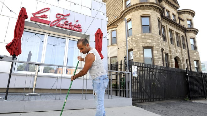 Elias Khalil sweeps in front of his restaurant, La Feria Spanish Tapas. As the Cass Corridor becomes more gentrified, crime has been going down.