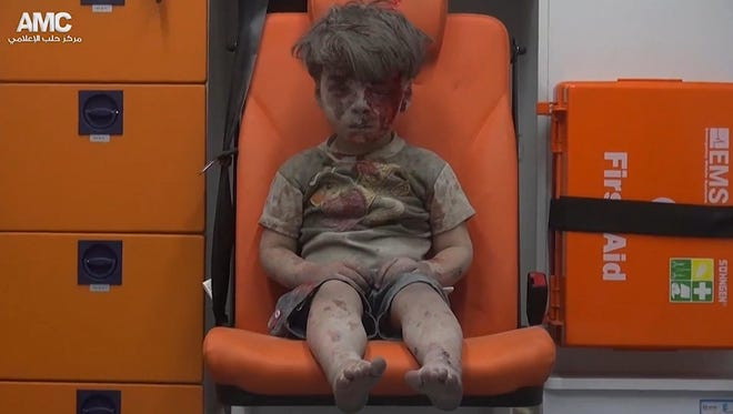 Omran Daqneesh, 5, sits in an ambulance after an airstrike hit the building he was in. An image taken from video provided by the Syrian anti-government activist group Aleppo Media Center shows 5-year-old Omran Daqneesh sitting in an ambulance after being pulled out or a building hit by an airstrike in Aleppo, Syria, on Aug. 17.