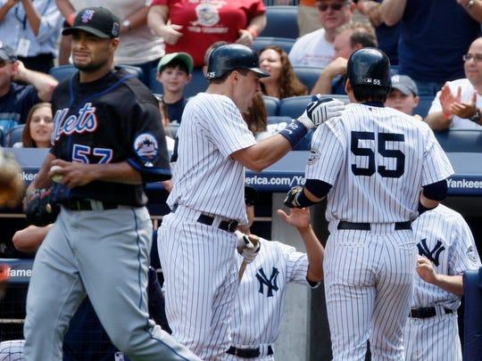 Yankees Mark Teixeira, center, congratulates Hideki Matsui (55) after he scored on Derek Jeter's RBI-single as Mets pitcher Johan Santana walks back to the mound in the Yankees' 15-0 shutout at Yankee Stadium on June 14, 2009.