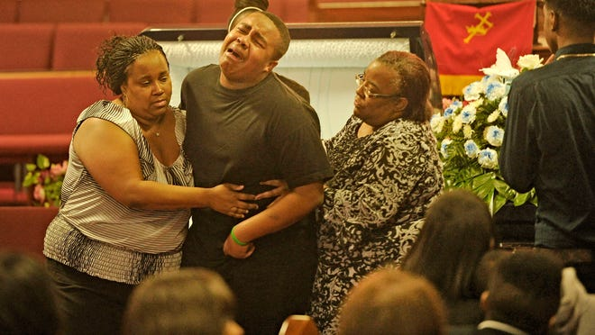 Michael Oglesby, 15-year-old Da'Vontae Ziegler's best firend, is helped away from Ziegler's casket by his mother, Crystal Greer, left, and Chatonya Beasley.