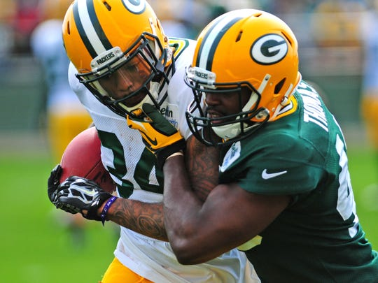 Green Bay Packers running back Rajion Neal, left, and linebacker Joe Thomas work on tackling drills during training camp practice at Ray Nitschke Field on Monday, July 28, 2014.
