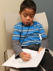 """Jonathan Lopez, 6, with gauze peeking from his mouth after his own dental treatment, waits as his brother gets fillings at the Delaware State Dental Society's annual """"Give Kids a Smile"""" event in Dover."""
