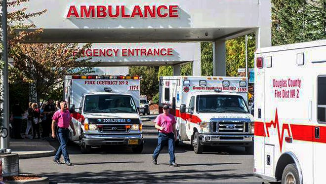 Paramedics return to their ambulances after delivering patients to Mercy Medical Center in Roseburg, Ore., following a deadly shooting at Umpqua Community College on Oct. 1, 2015.