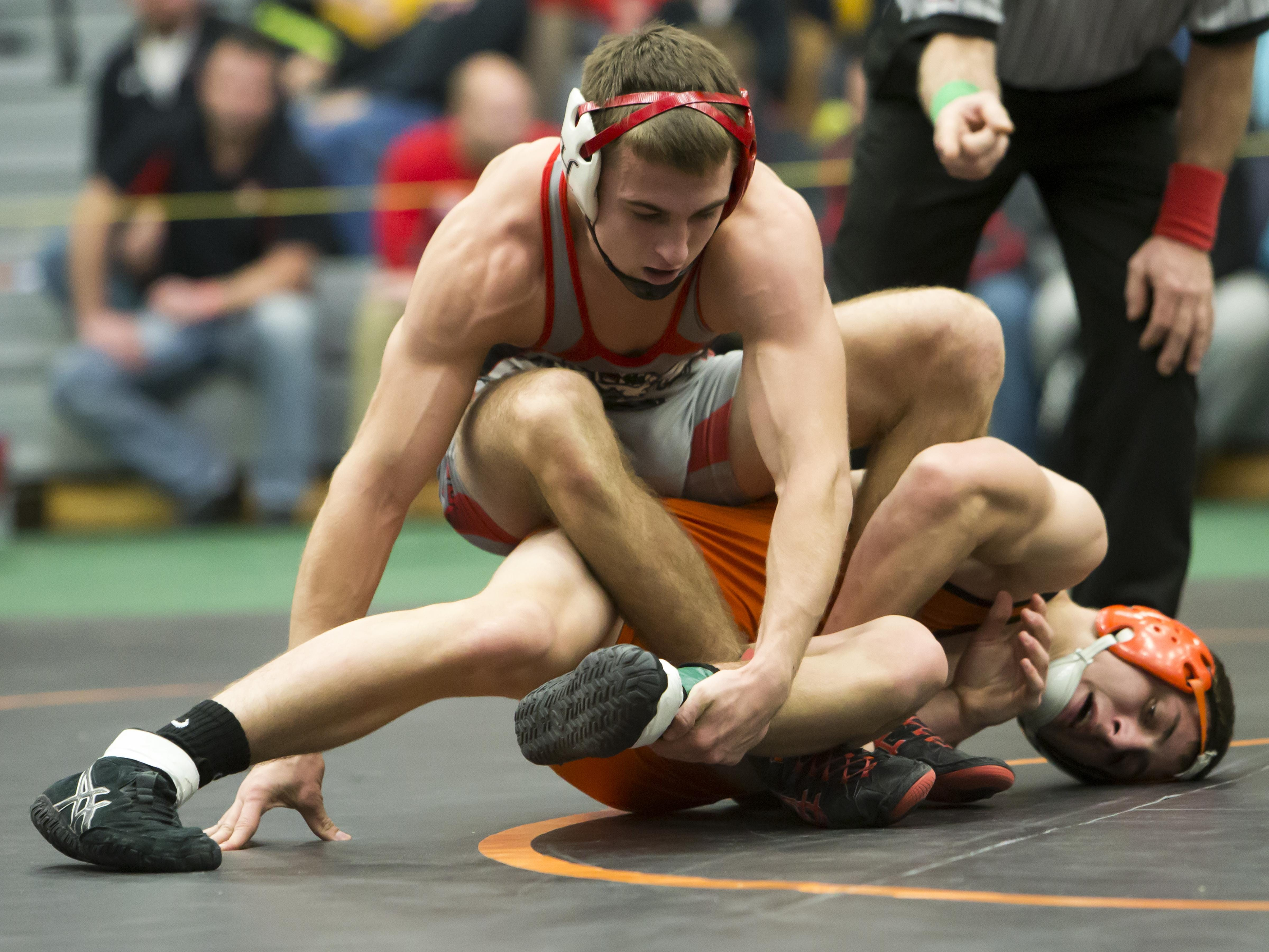 Nathan Lichtfuss of Hortonville (top) battles Bryce Ash of Oconto Falls at 145 pounds at the Oshkosh Lourdes On The Water Classic on Friday at Kolf Sports Center.