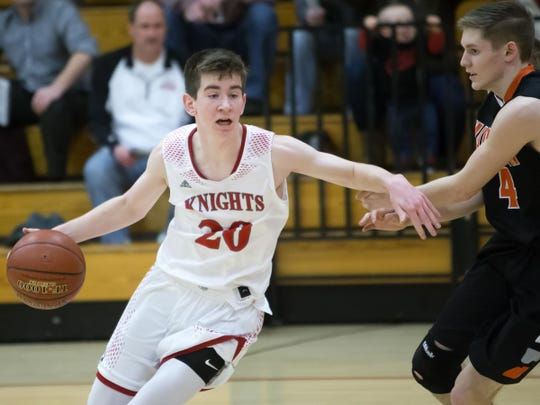 Lourdes Academy's Henry Noone (20) looks to drive around Horicon's Connor Drews on Tuesday night. Noone scored 23 points to lead the Knights to the win.