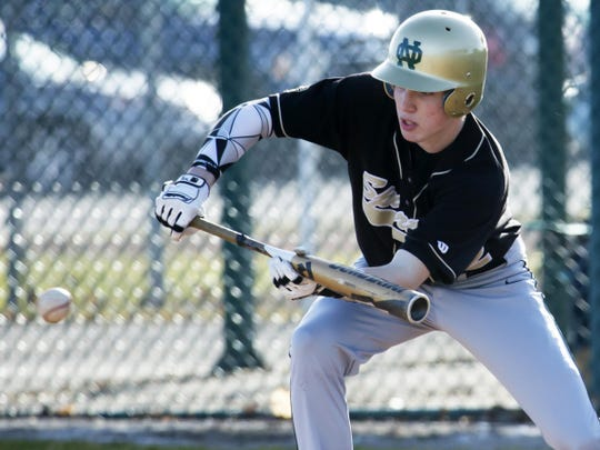 Oshkosh North's Brett Ellestad (22) lays down a bunt for a base hit to start a three-run rally in the second inning on Friday.