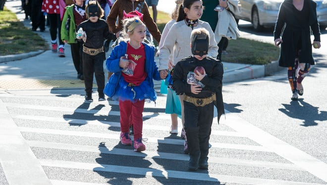 Students from Saint Francis de Sales Catholic School walk along West Carroll Street dressed in costume on Tuesday, Oct. 31, 2017.