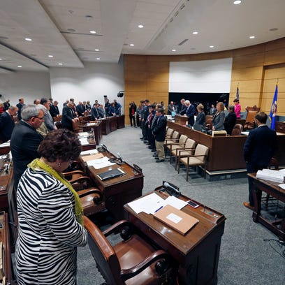 State senators bow during the opening prayer at the temporary Senate chamber in the new State Senate building as the 2016 legislative session got underway in St. Paul.