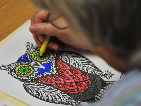 Eleanor Boening works on an owl at a coloring class
