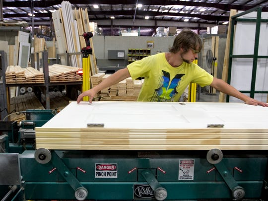 Andrew Duis works on the interior door line at Raymond Building Supply, which is benefiting from a construction uptick.