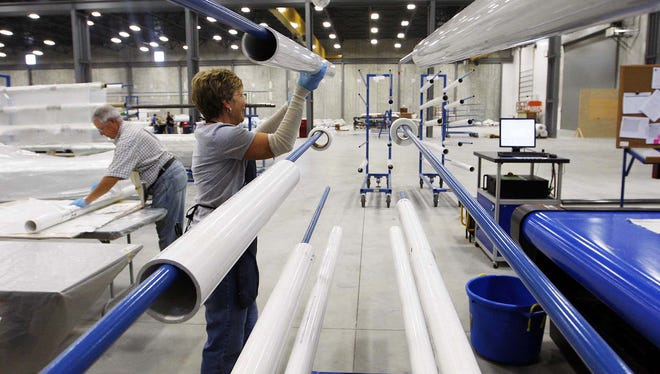 Pipe used to roll fiberglass is placed on a holder inside the TPI Composites wind turbine fabrication plant in Newton. The wind energy industry has replaced a fraction of the jobs lost when the Maytag plant closed down.