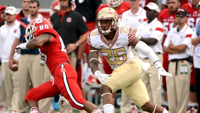 Florida State Seminoles cornerback P.J. Williams (26) defends North Carolina State Wolfpack wide receiver Bryan Underwood (80) during the first half at Carter Finley Stadium.