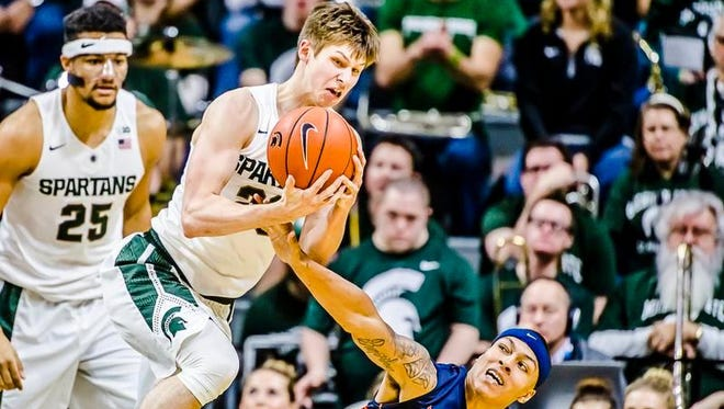 Matt McQuaid ,center, of MSU comes away with the ball after an MSU triple team of Khalid Lewis ,3, of Illinois forced a turnover in the 2nd half of their game Thursday January 7, 2016 in East Lansing.