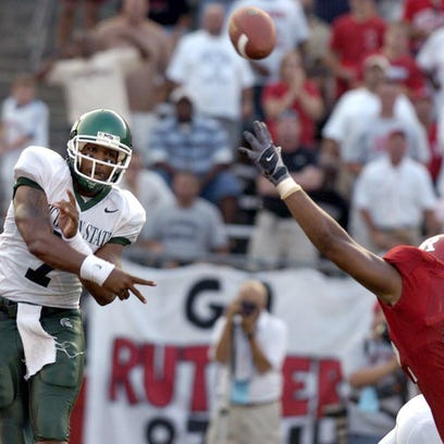 MSU's Damon Dowdell unloads a short pass over Rutgers' Alfred Peterson in the Spartans' 2004 loss at Rutgers. Dowdell's late INT to a defensive lineman ended the Spartans' chances.