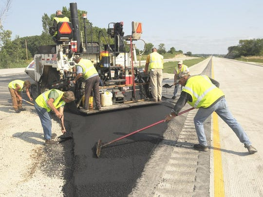 Road construction crew from North East Asphalt blacktop