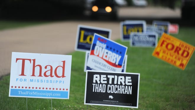 Campaign signs line the driveway to the voting precinct located at the Victory Community Church building on Old Canton Road in Madison.