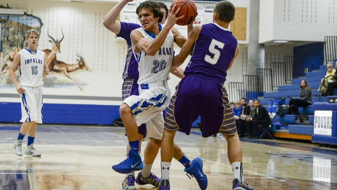 Poudre's Anthony Raffaeli breaks past Holy Family's Alex Comeaux and Joe Golter in the FCHS & PHS Boys Basketball Shootout, Tuesday, Dec. 9, 2014, in Fort Collins, CO.