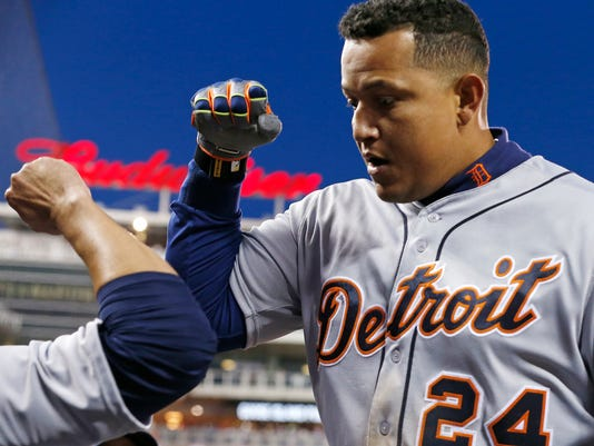 Detroit Tigers' Miguel Cabrera is congratulated in the dugout after his solo home run off Minnesota Twins pitcher Phil Hughes in the fifth inning of a baseball game Friday, April 29, 2016, in Minneapolis. (AP Photo/Jim Mone)