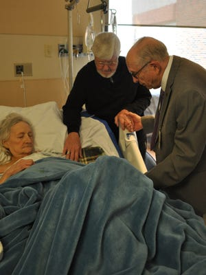 Murray Smith (right) concludes his visit to Judith Batson (left) and her husband Yvon with a prayer. In 1992, Smith started working with the Rapides Regional Medical Center volunteer chaplain program, and at 90, he still makes his rounds twice each week.