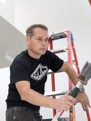 "Shepard Fairey setting up his exhibit, ""Shepard Fairey: Salad Days, 1989-1999,"" at the Cranbrook Art Museum in Bloomfield Hills in 2018."