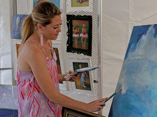 Melissa Prigmore paints in her booth at Art & Soul Festival Saturday, June 23, 2018, at Indiana Street between 10th and Ninth streets.