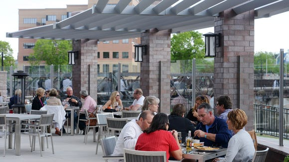 Customers dine along the river on the patio Thursday at Elements on 8th, May 21, 2015.