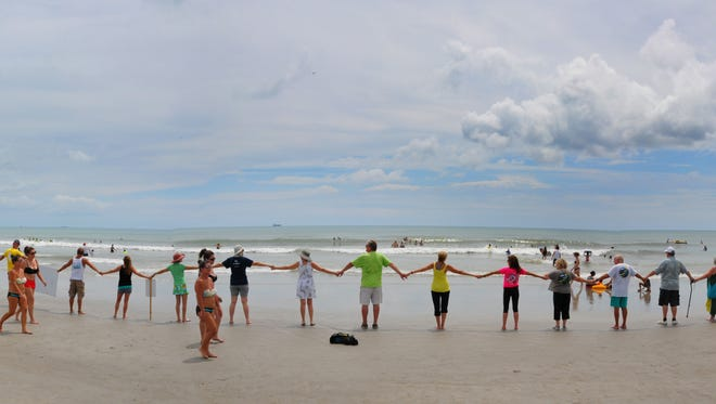 About 75 enthusiastic people showed up for Hands Across the Sand at Lori Wilson Park in Cocoa Beach Saturday, to show their support for the environment and stand against offshore drilling and offshore seismic testing.