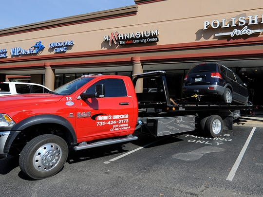 A wrecker works on removing an SUV from Polished Salon off of Union University Drive in Jackson, Tenn., on Thursday, Sept. 22, 2016.
