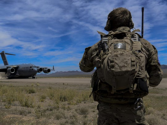 A combat controller watches as a C-17 assigned to the 17th Weapons Squadron at Nellis Air Force Base, Nev., lands on an airstrip in the Nevada Test and Training Range during Joint Forcible Entry Exercise, June 16, 2016. The exercise demonstrates the Air Force's ability to tactically deliver and recover combat forces via air drops and combat landings in a contested environment.