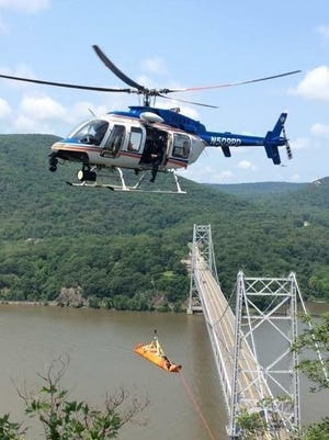 A Westchester County police helicopter rescues an injured hiker,Thomas Javenes of Stony Point,  from steep terrain near the Anthony's Nose peak in Hudson Highlands State Park in Cortlandt, July 5, 2015. The Bear Mountain Bridge is in the background.